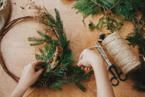 Hands holding fir branches and pine cones, berries, thread, scissors on wooden table. Making rustic christmas wreath flat lay. Details for christmas wreath workshop